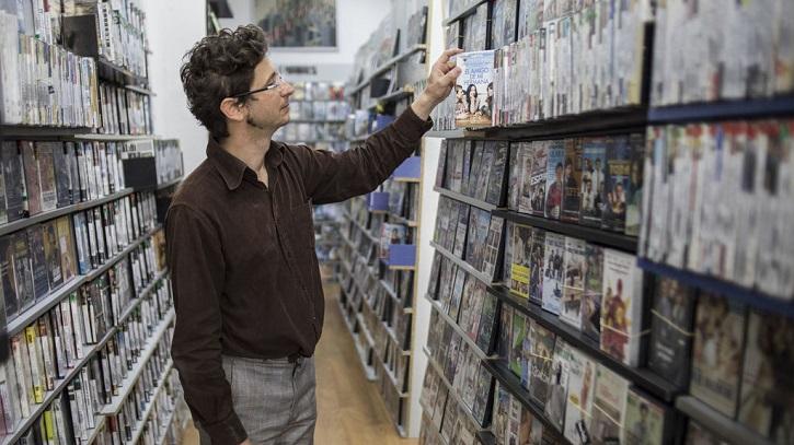 Andrés Santana, dueño de 'Ficciones de Cine', revisa su catálogo   Cierra 'Ficciones de Cine', el último videoclub de Malasaña